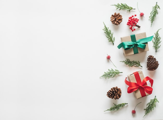 Weihnachtshintergrund mit tannenzweigbaum-tannenzapfengeschenk und geschenk über weißem hintergrund.