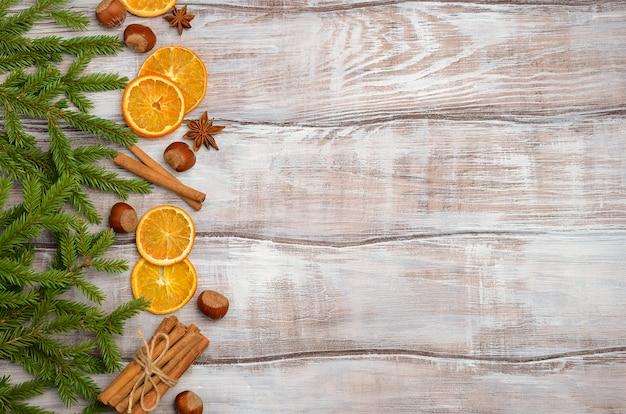 Weihnachtshintergrund mit tannenzweigen, nüssen, gewürzen und getrockneten orangen.