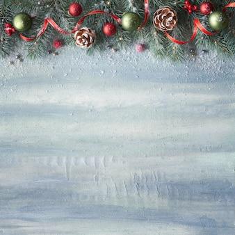 Weihnachtshintergrund mit tannenzweigen, roten beeren, zapfen und bändern auf rustikalem holzhintergrund mit textraum.