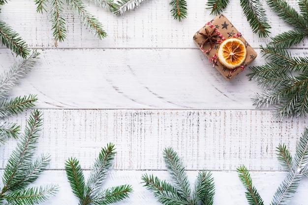 Weihnachtshintergrund mit tannenzweigen, tannenzapfen, geschenkbox, getrockneten orangen, sternanis und beeren auf dem alten weißen holzbrett. draufsicht.