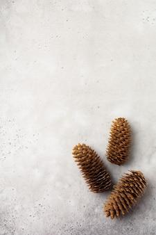 Weihnachtshintergrund mit tannenzweigen und -kegeln auf heller konkreter alter hintergrundtabelle. selektiver fokus. draufsicht mit kopienraum.