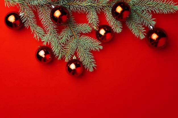Weihnachtshintergrund mit tannenzweigen und kugeln auf rotem papier