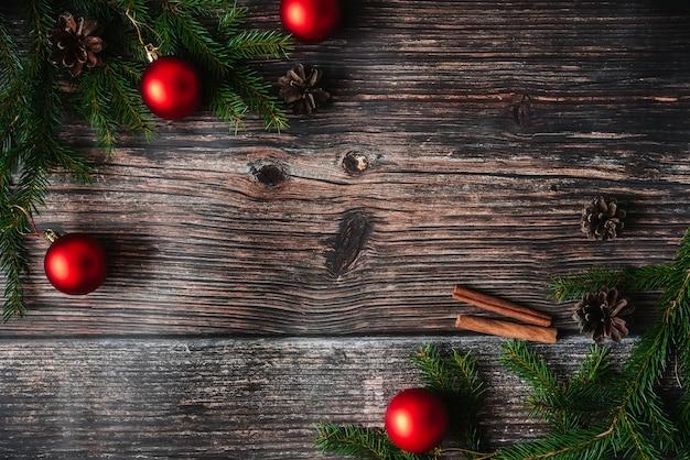 Weihnachtshintergrund mit tannenzweigen und roten bällen, kiefernkegel. dekorativer winterrahmen