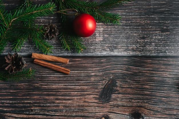 Weihnachtshintergrund mit tannenzweigen und roten bällen, kiefernkegel