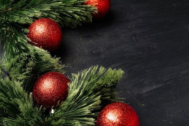Weihnachtshintergrund mit tannenzweigen und roten kugeln auf schwarz mit kopienraum