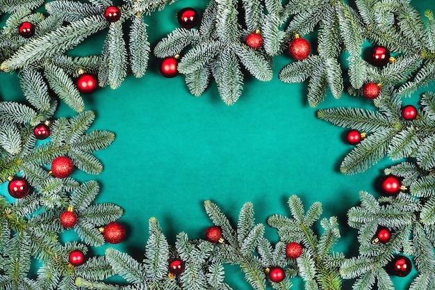 Weihnachtshintergrund mit tannenzweigen und roten kugeln.