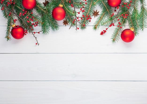 Weihnachtshintergrund mit tannenzweigen und roten weihnachtskugeln, berberiszweige mit frucht und sternanis auf weißem hölzernem hintergrund