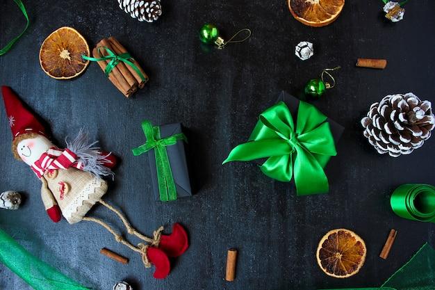 Weihnachtshintergrund mit trockener orange, weißer tannenzapfen, grünen christbaumkugeln, mandarinen, rotem apfel, ingwerstangen,
