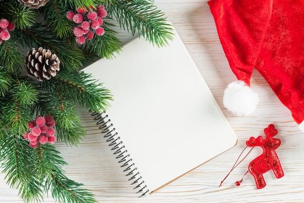 Weihnachtshintergrund mit weihnachtsbaum und leere grußgrußkarte auf weißer holzoberfläche.