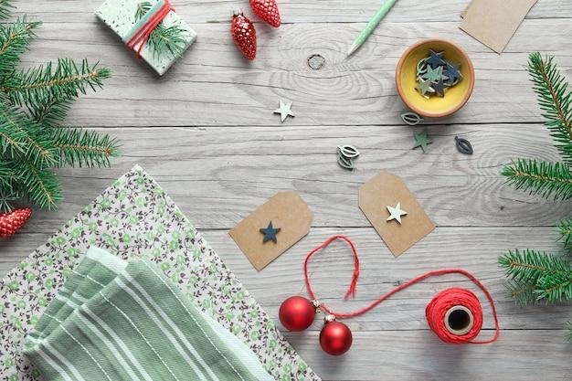 Weihnachtshintergrund mit weihnachtsbaumtannenzweigen, geschenkboxen und dekorationen in rot, weiß und grün. diy null abfall dekorationen zu hause machen.