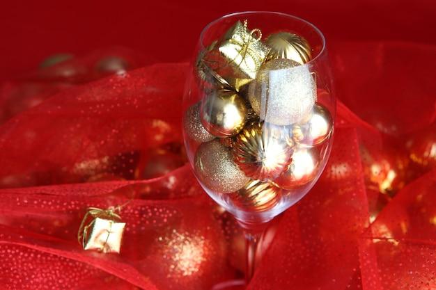Weihnachtshintergrund mit weinglas und goldenen weihnachtsdekorationen darin weinglas mit christus...