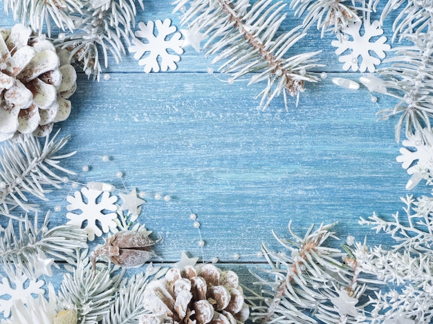 Weihnachtshintergrund mit weißen fichtenzweigen und schneeflocken auf einem blauen hölzernen hintergrund