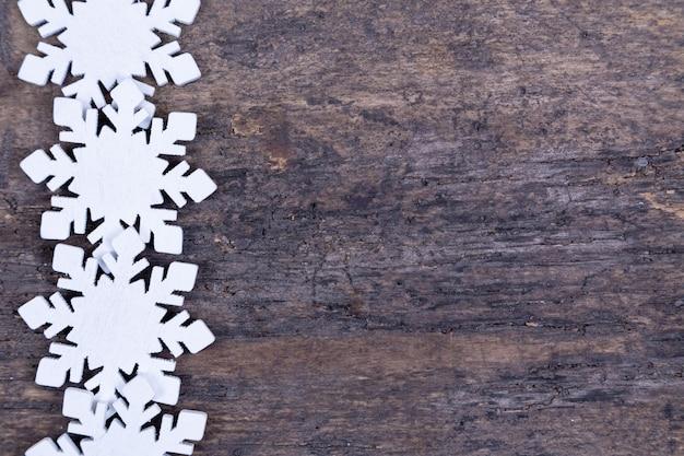 Weihnachtshintergrund mit weißen schneeflocken, die in einer linie gelegt werden, weihnachtsrahmen des hölzernen spielzeugs. weihnachtshintergrund mit weißen schneeflocken, weihnachtsrahmen aus holzspielzeug