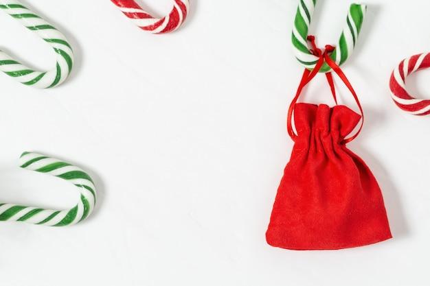 Weihnachtshintergrund mit zuckerstangen und geschenk in der kleinen roten tasche