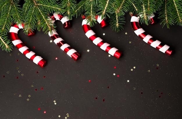 Weihnachtshintergrund mit zuckerstangen und tannenzweigen