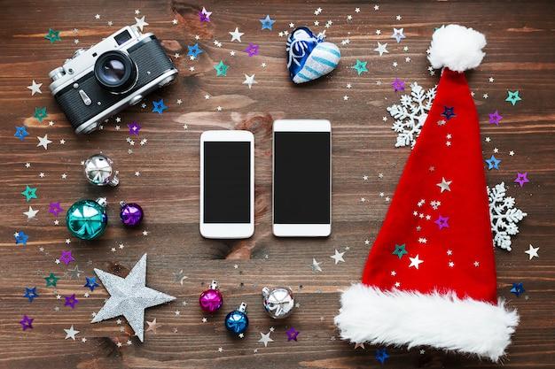 Weihnachtshintergrund mit zwei smartphones, altmodische kamera, roter sankt hut, dekorationen