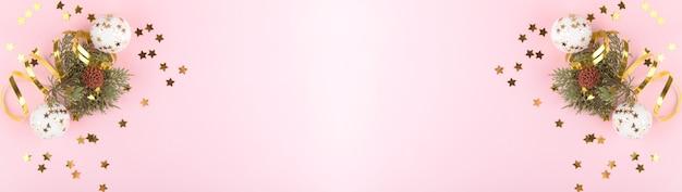Weihnachtshintergrund. natürliche tannenzweige mit goldenen weihnachtskugeln und goldener dekortation auf rosa pastellhintergrund