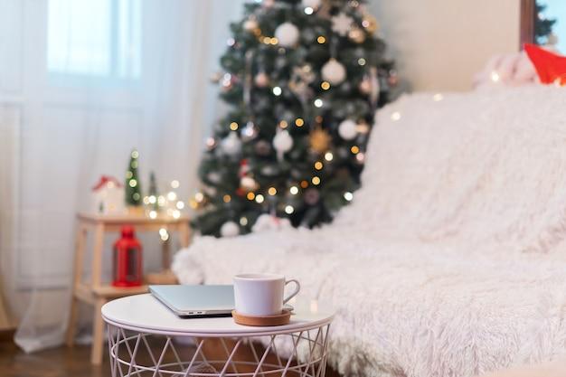Weihnachtshintergrund oder grußkarte mit laptop und kaffeetasse zu hause