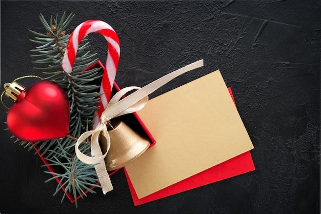 Weihnachtshintergrund: rote geschenkbox mit einem weihnachtsspielzeug in form eines herzens, einer goldenen glocke, tannenzweigen und einer karte für glückwunschtext