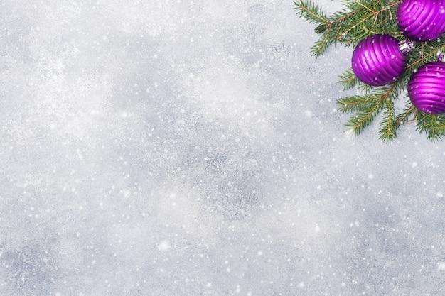 Weihnachtshintergrund, -spielwaren und -niederlassungstanne auf grau