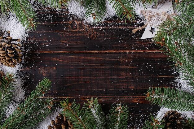 Weihnachtshintergrund, -tannenbäume und -kegel auf einem holztisch, zerquetscht durch weißen schnee, kopienraum, draufsicht.