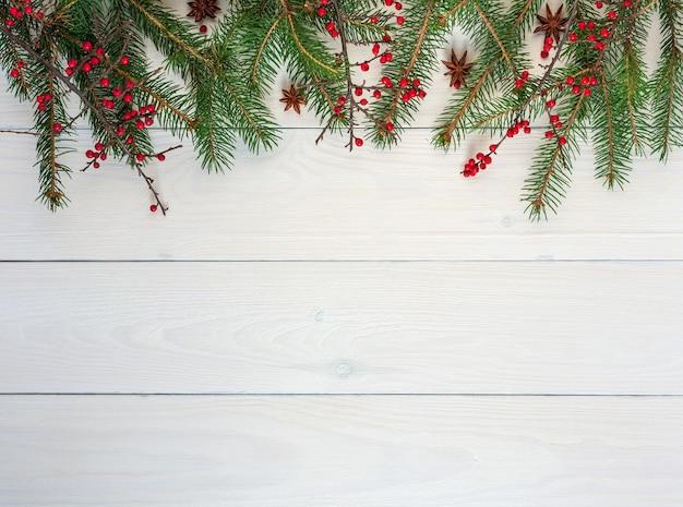Weihnachtshintergrund, tannenzweige und berberiszweige mit roten früchten und sternanis auf weißem hölzernem hintergrund