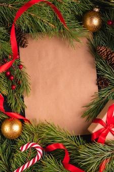Weihnachtshintergrund verziert mit tannenzweigen, spielzeugen, süßigkeiten und geschenkbox