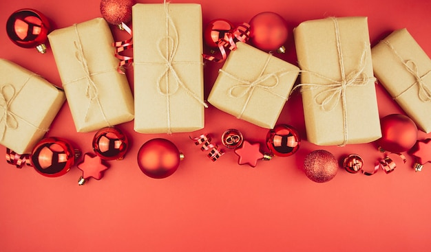 Weihnachtshintergrund von geschenkboxen, roten kugeln, serpentin auf einem roten hintergrund. speicherplatz kopieren.