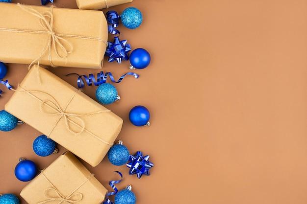 Weihnachtshintergrund von geschenkboxen und blauen kugeln auf einem braunen tisch. weihnachtshintergrund. banner.