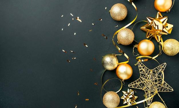 Weihnachtshintergrund von goldkugeln, serpentin auf einem dunklen hintergrund. weihnachtskarte. speicherplatz kopieren.