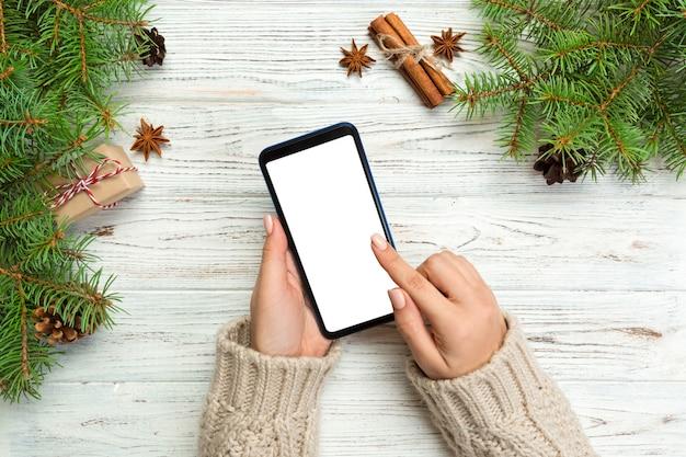 Weihnachtshintergrund, weibliche hände, die smartphone nachrichten