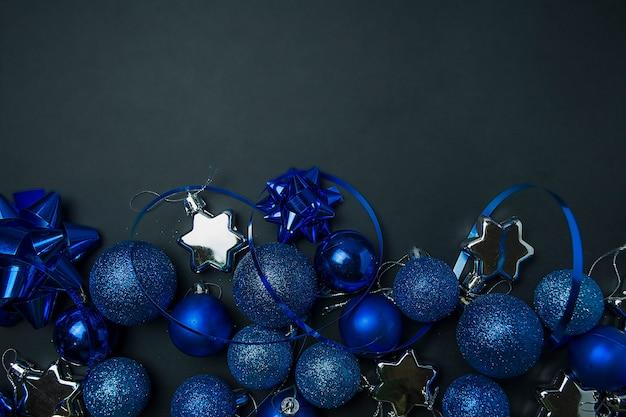 Weihnachtshintergrund weihnachtsblaue deko-bubbler auf einem dunklen schwarz