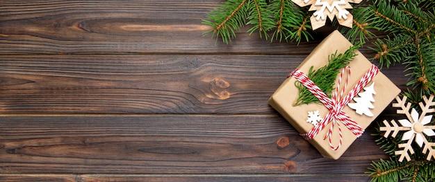 Weihnachtshintergrund weihnachtsgeschenk mit tannenzweigen und schneeflocke auf hölzernem weißem hintergrund mit fahne copyspace ebenenlage, draufsicht