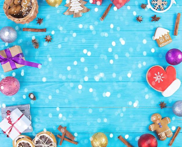 Weihnachtshintergrund. weihnachtsgeschenk, spielzeug, lebkuchen, gewürze und dekorationen auf holztisch. draufsicht