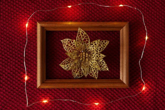 Weihnachtshintergrund weihnachtsspielzeugrahmen und -girlande, die auf der gestrickten beschaffenheit eines pullovers liegen