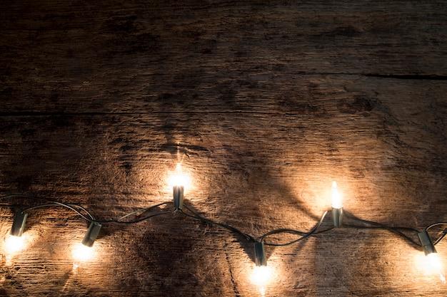 Weihnachtshintergrund - weinlese planked holz mit lichtern und raum des freien texts.