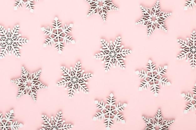Weihnachtshintergrund. weiße schneedekorationen auf einem rosa hintergrund.