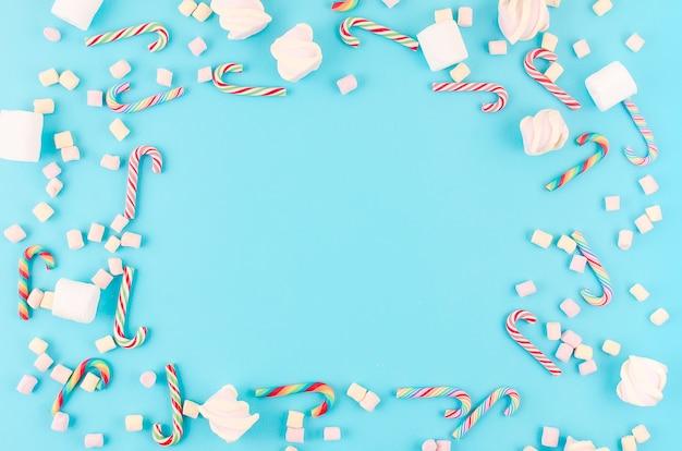 Weihnachtshintergrund. zuckerkaramellrohr und eibisch auf pastellblauem hintergrund.