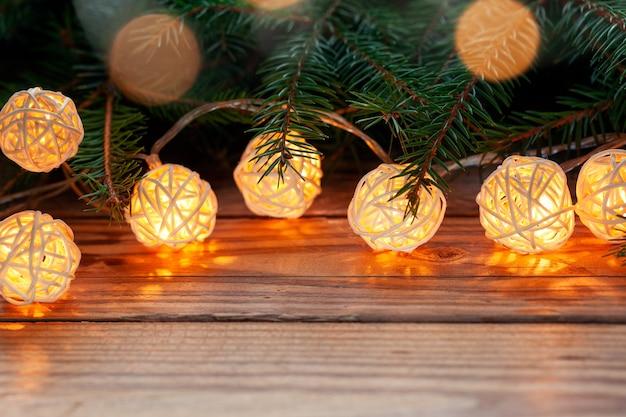 Weihnachtshintergrundfeiertag mit dekorationsgirlande lichter auf holztisch