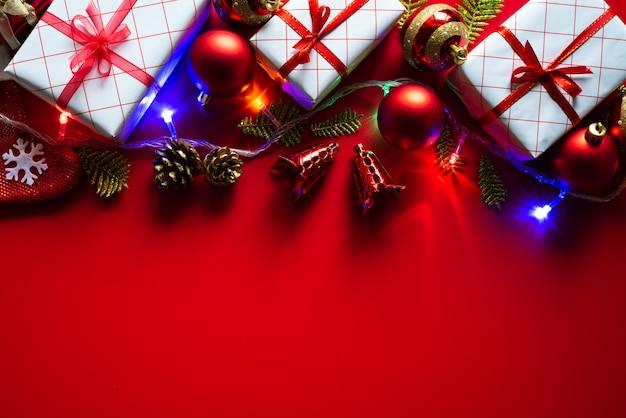 Weihnachtshintergrundgeschenkbox mit roten ball- und kiefernkegeln auf rotem hintergrund.
