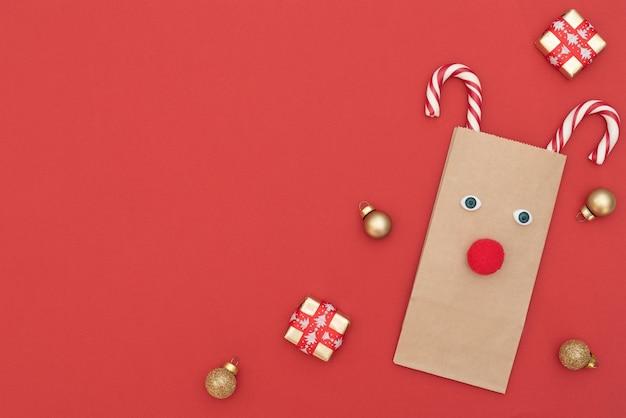 Weihnachtshirsch aus bastel-einkaufstasche und zwei weihnachtsstöcken mit geschenkboxen und goldkugeln