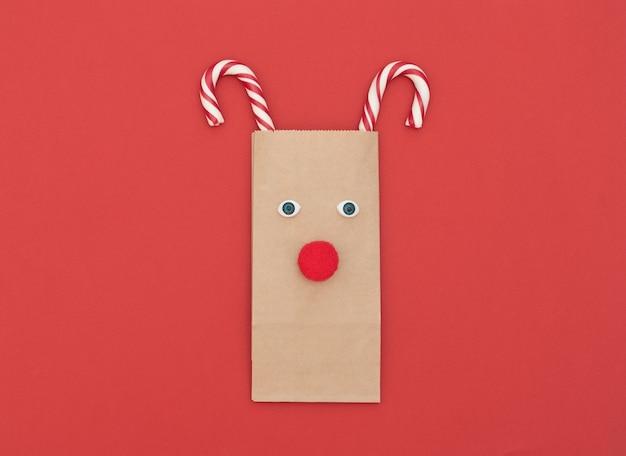 Weihnachtshirsch aus handwerklicher einkaufstasche und zwei weihnachtsstöcken auf rotem hintergrund.