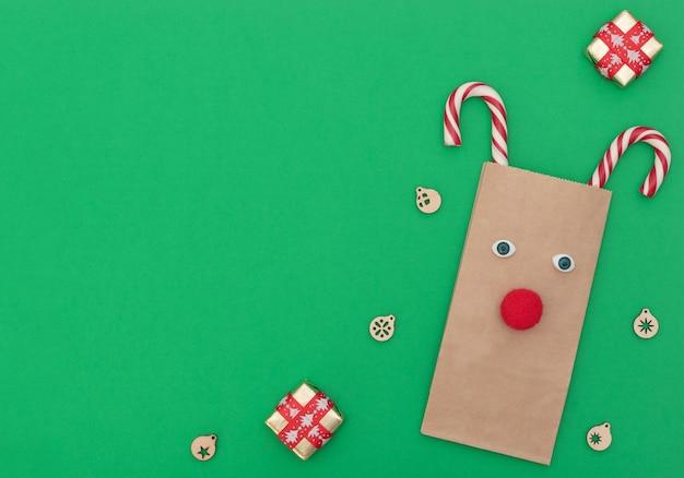 Weihnachtshirsch aus handwerklicher einkaufstasche und zwei weihnachtsstöcken mit weihnachtsdekor auf grünem hintergrund.