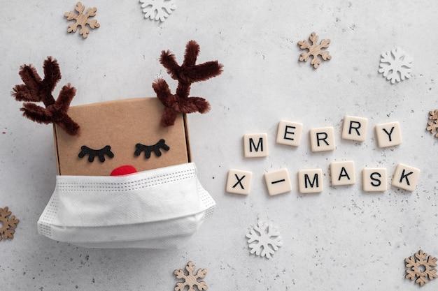 Weihnachtshirsch-geschenkbox mit einer medizinischen maske.