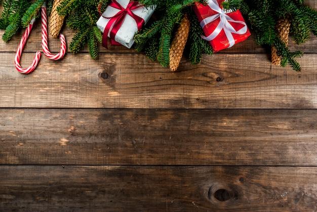 Weihnachtshölzerner hintergrund mit tannenbaumasten, kiefernkegeln und christbaumkugeln kopieren raum über rahmen
