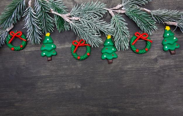 Weihnachtshölzerner hintergrund mit weihnachtsbaum und roten dekorationen.