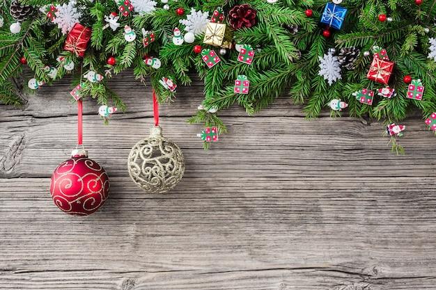 Weihnachtsholz mit tannenzweigen verziert mit weihnachtsschmuck