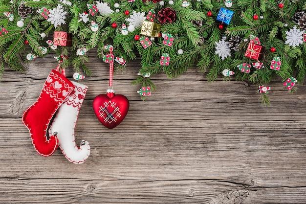 Weihnachtsholz mit tannenzweigen verziert mit weihnachtssocken