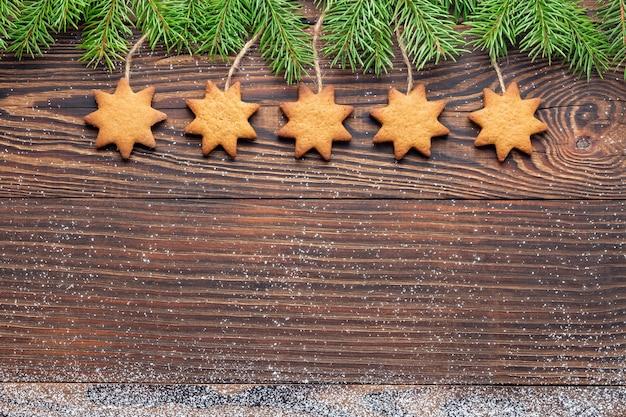 Weihnachtsholzhintergrund mit hausgemachten sternförmigen keksen, die zwischen tannenzweigen hängen
