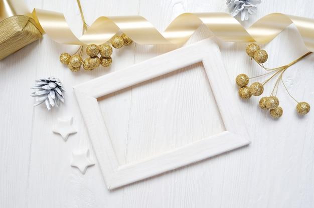 Weihnachtsholzrahmengoldbogenband und baumkegel